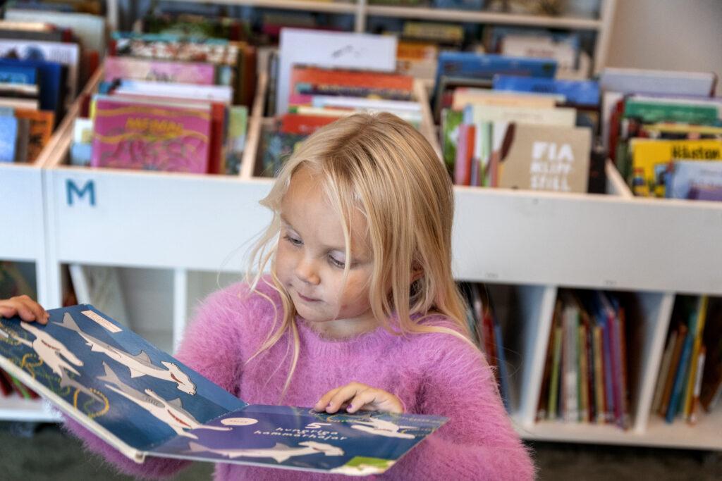 Barn läser bok på ett bibliotek