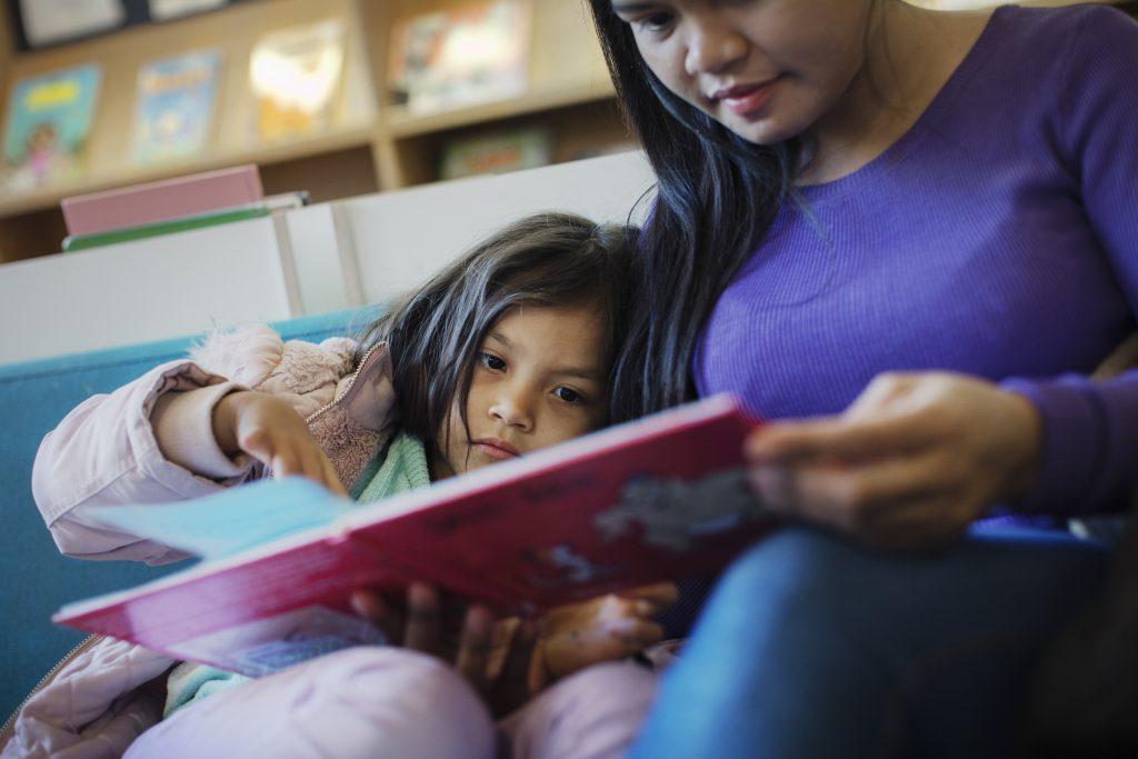 En kvinna med lila tröja som läser en bilderbok tillsammans med ett barn i femårsåldern. Båda ser allvarliga ut. Barnet pekar på en sida i boken.