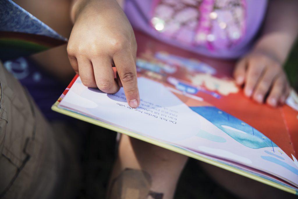 En barnhand som pekar på bokstäverna i en bilderbok
