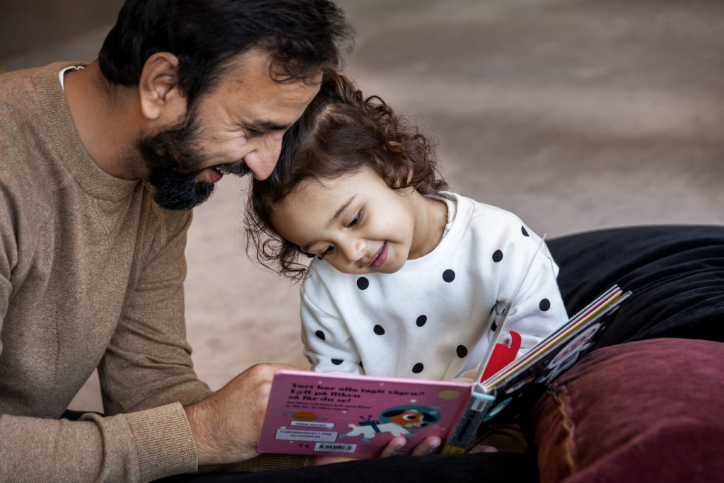 En man med mörkt skägg som tittar i en bilderbok tillsammans med ett barn i treårsåldern. Båda ser glada ut.