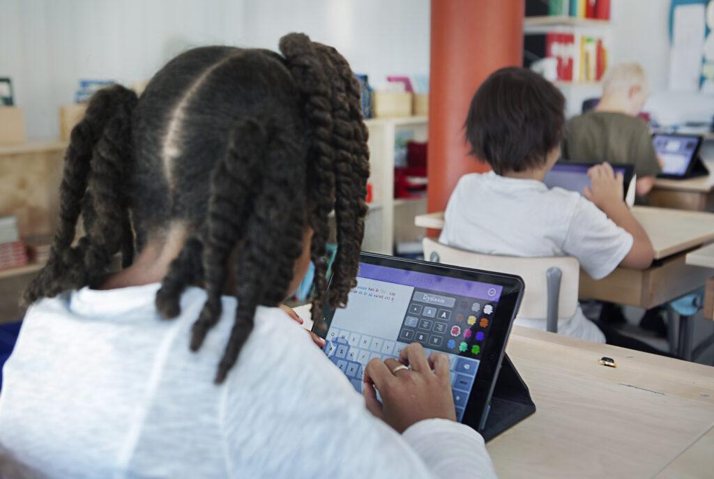 Ett barn med flätor som skriver på en läsplatta. Barnet sitter i en skolbänk bakom andra barn.