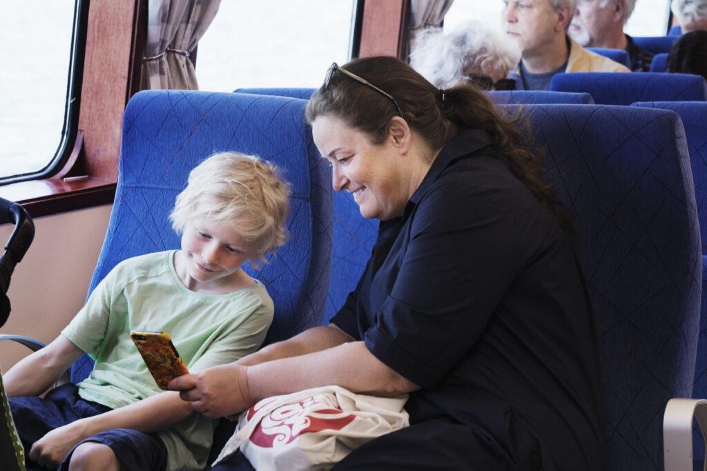 Ett barn och en vuxen tittar tillsammans på en mobiltelefon. Båda ser glada ut.