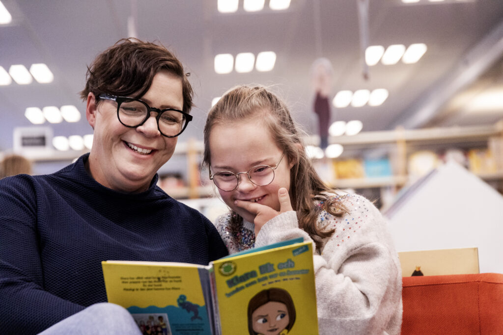 En vuxen som tillsammans med ett barn läser en bok. Boken är gul. Båda ser glada ut.