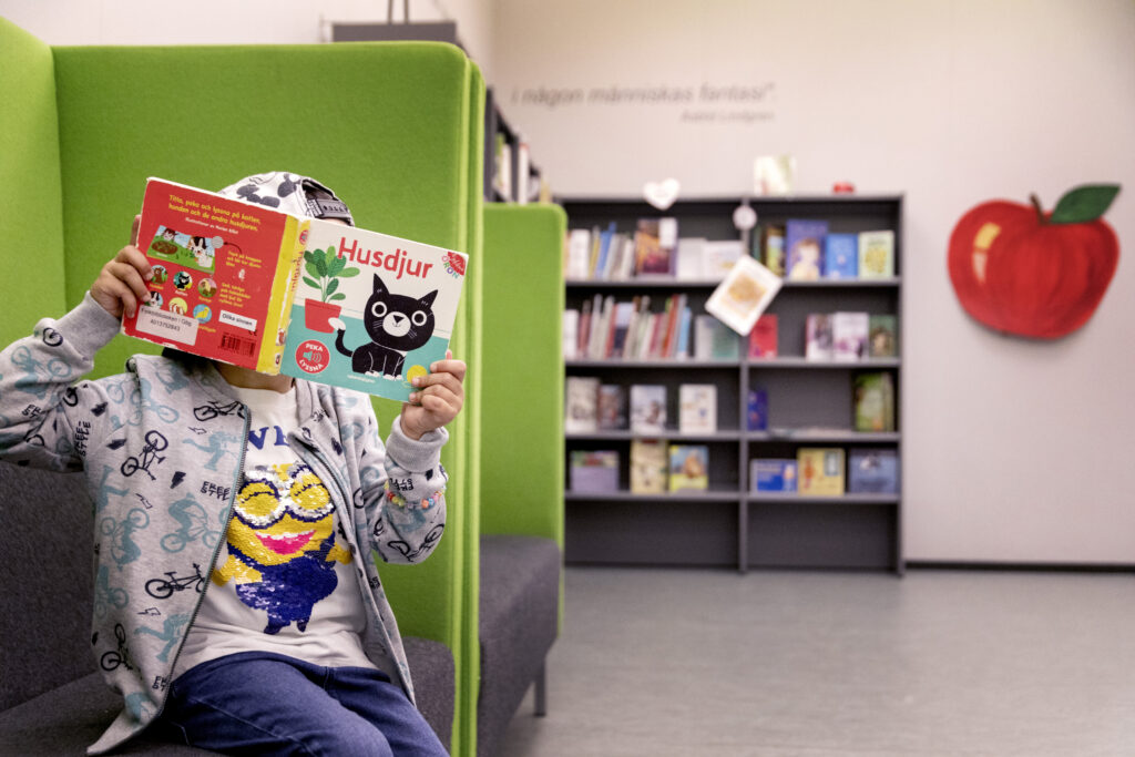 Ett barn som håller upp en pekbok framför sitt ansikte. Barnet är på biblioteket på avdelningen för tillgänglig litteratur, den så kallade äppelhyllan. På bokens framsida syns en bild av en katt.