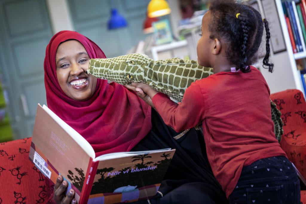 Mamma och barn leker med bok