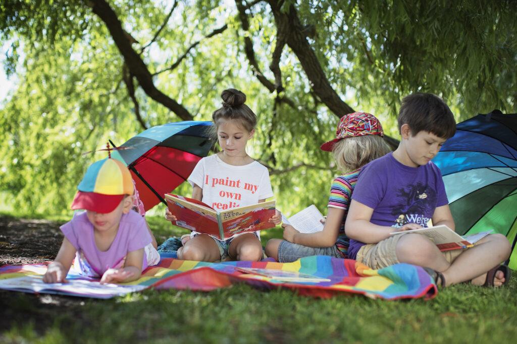 Barn läser böcker i en park med regnbågsfärgade paraplyer
